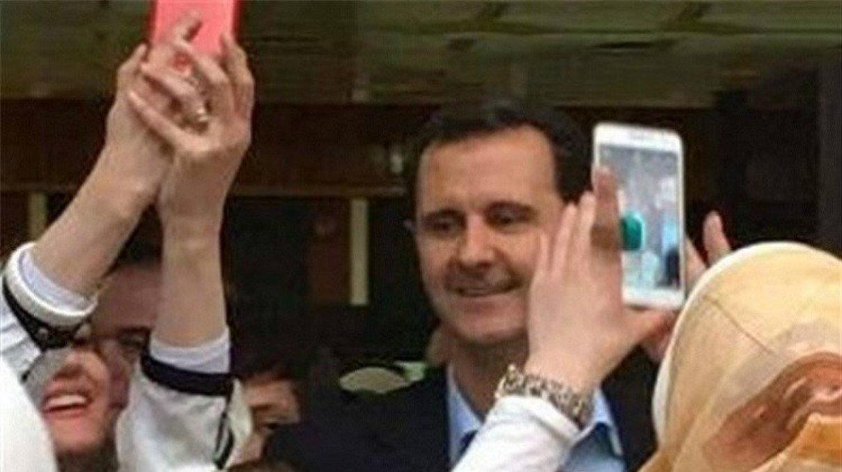 Des Syriens photographient le président Assad