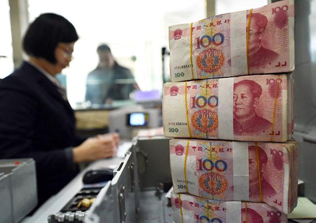 Un employé qui compte  des billets de banque dans une banque de 100 yuans (14 euros) à Lianyungang, dans l'Est de la province du Jiangsu le 7 Janvier 2016