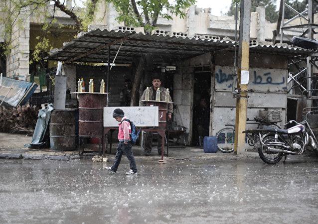 Un écolier syrien marche sous la pluie à Kafr Batna, dans la région de Ghouta orientale, à la périphérie de la capitale Damas (File)
