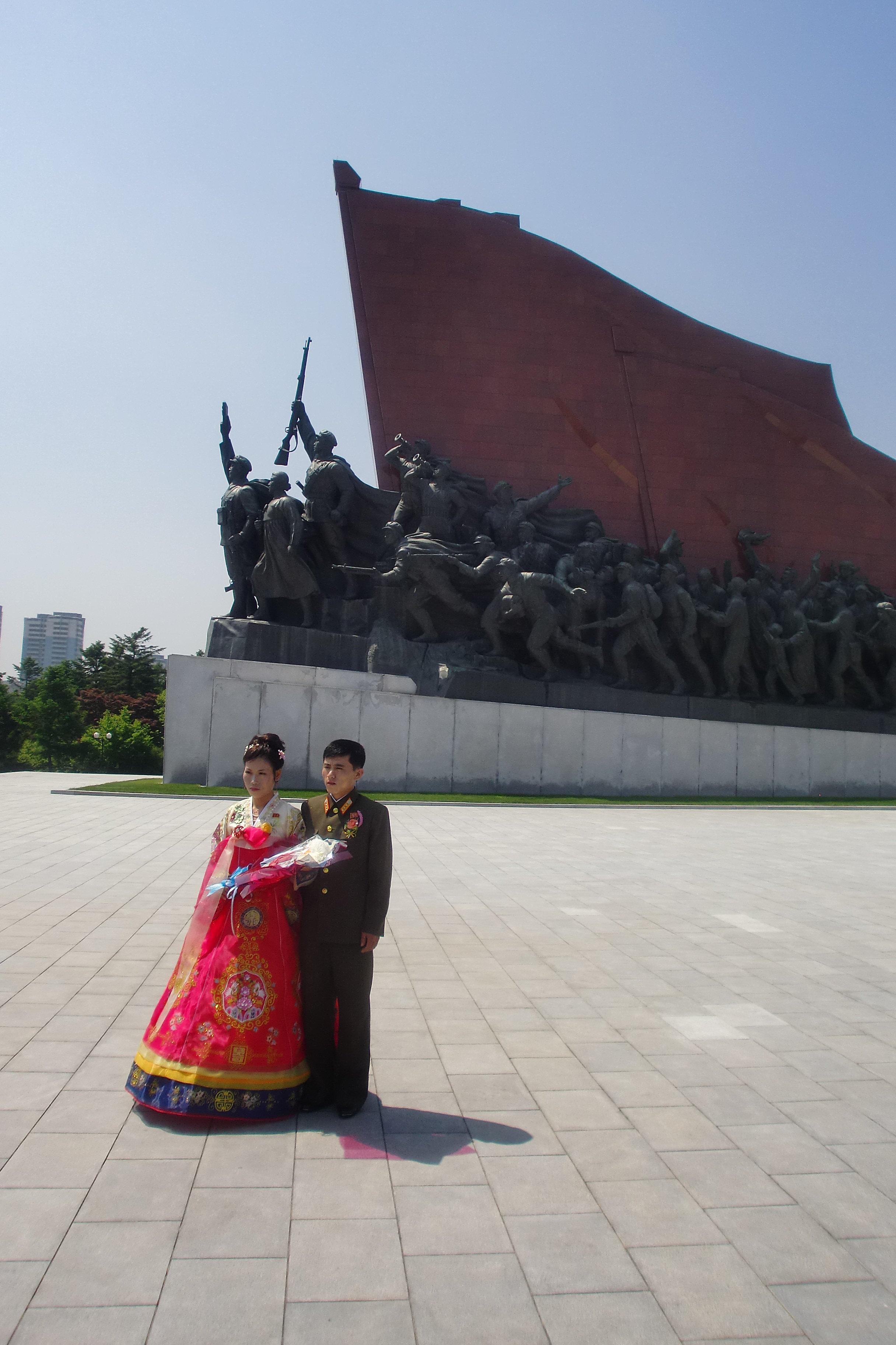 Des jeunes mariés devant un monument à Pyongyang