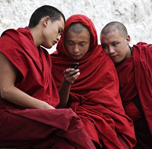 Des moines bouddhistes devant un portable