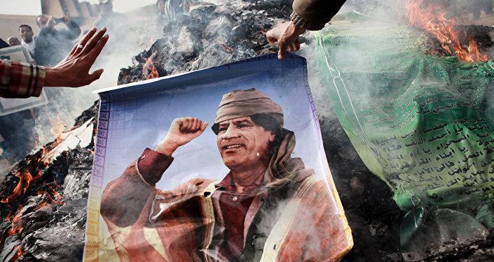 Un habitant de Benghazi (Libye) brûlant un portrait de Mouammar Kadhafi