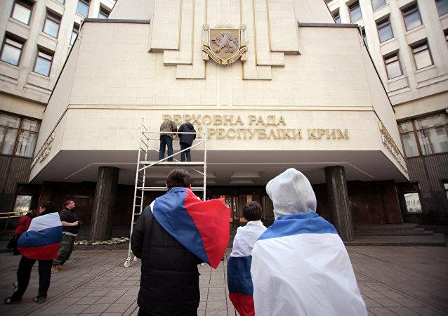 Des ouvriers enlèvent un panneau en ukrainien au siège du parlement criméen