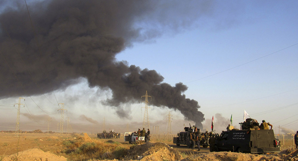 Smoke rises from Islamic State group positions after an airstrike by U.S.-led coalition warplanes in Fallujah, as Iraqi security forces and allied Shiite Popular Mobilization Forces and Sunni tribal fighters, take combat positions outside Fallujah, 40 miles (65 kilometers) west of Baghdad, Iraq, Monday, May 23, 2016