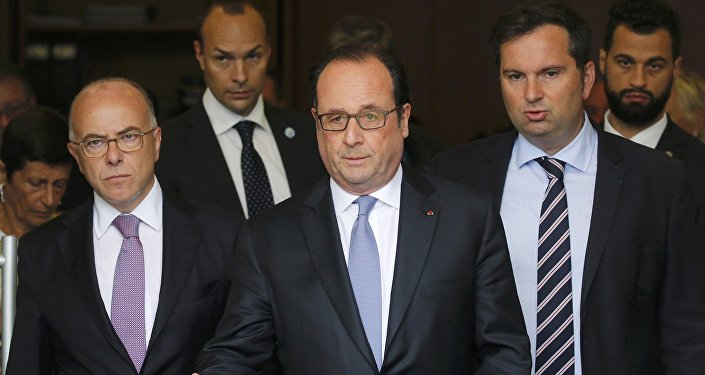 French President Francois Hollande (C), Interior Minister Bernard Cazeneuve (L) and French Interior Ministry spokesman Pierre-Henry Brandet (R) leave the city hall after two assailants had taken five people hostage in the church at Saint-Etienne-du -Rouvray near Rouen in Normandy, France, July 26, 2016.