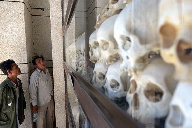 Des hommes cambodgiens regargent les crânes des victimes du régime des Khmers rouges