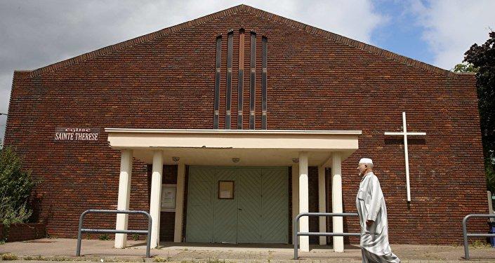 Un musulman passe devant l'église Saint-Thérèse de Saint-Etienne-du-Rouvray (Normandie)