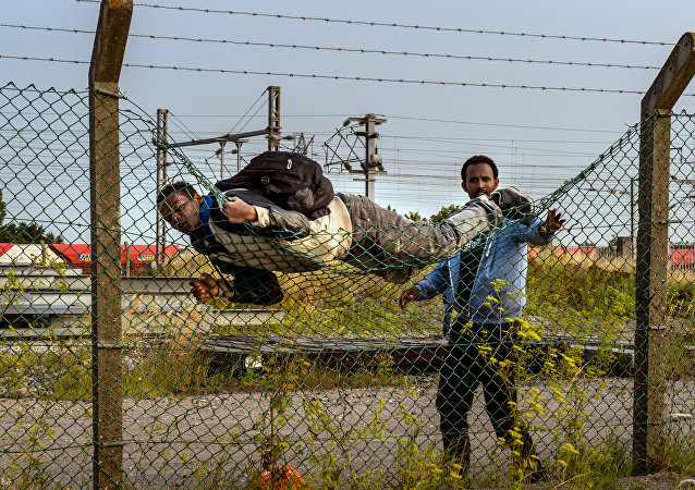 A migrant climbs over a fence in Coquelles, near Calais northern France