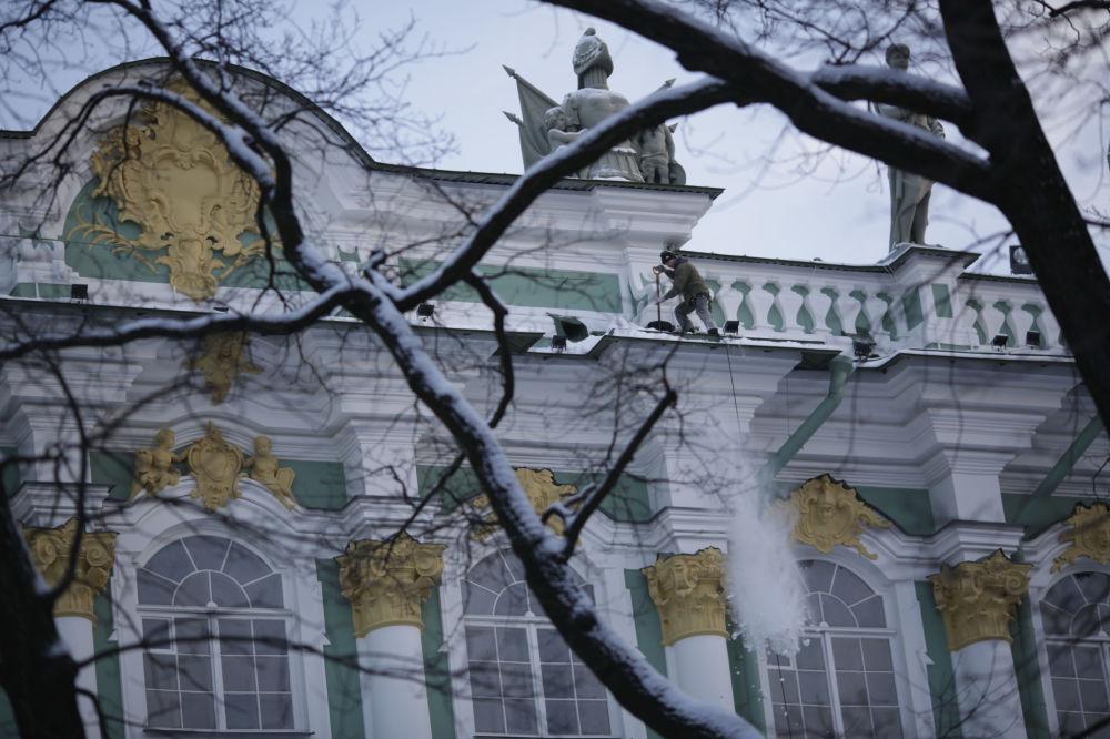 Un ouvrier déblaie la neige du toit de l'Ermitage à Saint-Pétersbourg