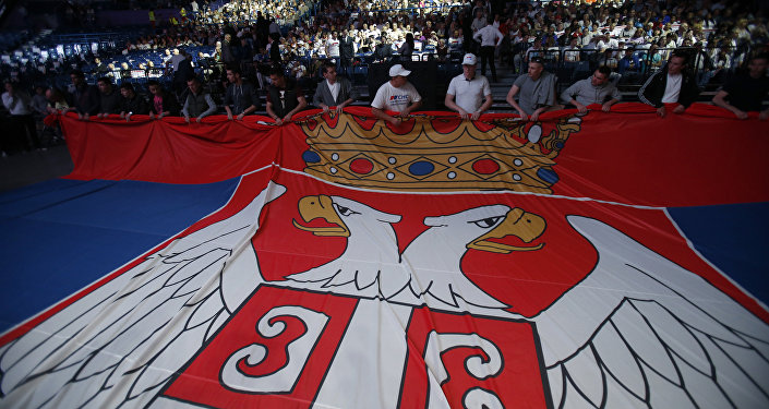 Serbian Progressive Party supporters hold Serbian flag during a pre-election rally in Belgrade, Serbia, Thursday, April 21, 2016
