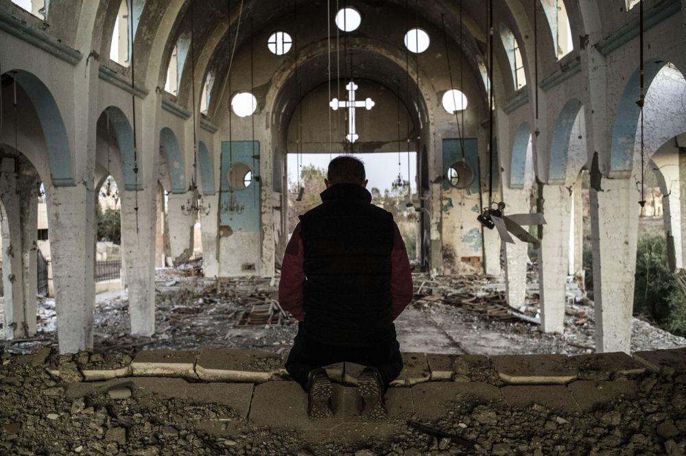 Un habitant d'un village de la province syrienne de Hassaké prie dans la cathédrale de Saint-Georges, détruite par Daech, le 8 décembre 2015