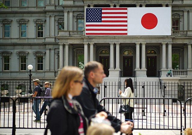 Les piétons passent devant les drapeaux des États-Unis et du Japon sur le bâtiment du bureau d'Eisenhower à côté de la Maison Blanche, le 27 avril 2015 à Washington, DC