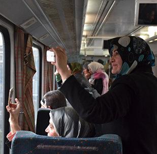Des passagères du train prennent en photo des quartiers d'Alep