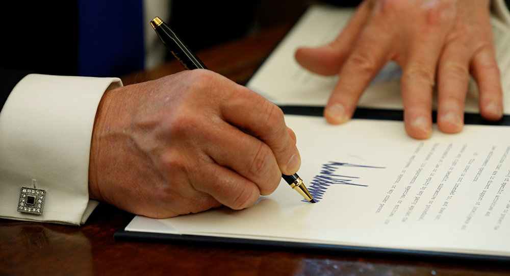 Donald Trump signe un document
