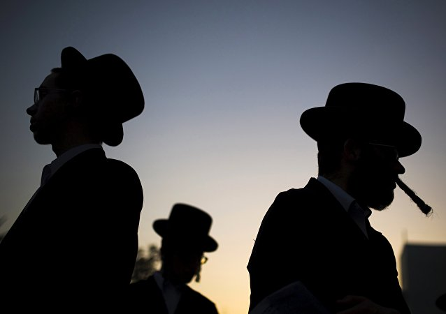 Ultra-Orthodox Jews pray during a protest against a shopping centre which opens on Saturdays