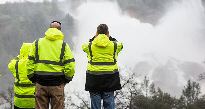 California Department of Water Resources personnel monitor water flowing through a damaged spillway on the Oroville Dam in Oroville, California, U.S., on February 10, 2017