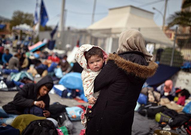 Une femme syrienne porte son enfant dans ses bras à Chios, le 3 avril 2016