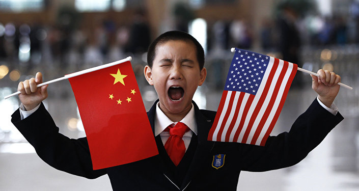 Un garçon tient des drapeaux chinois et américain à Pékin