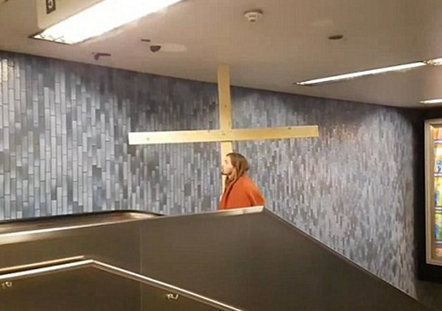 Un homme déguisé en Jésus coincé dans un escalier roulant