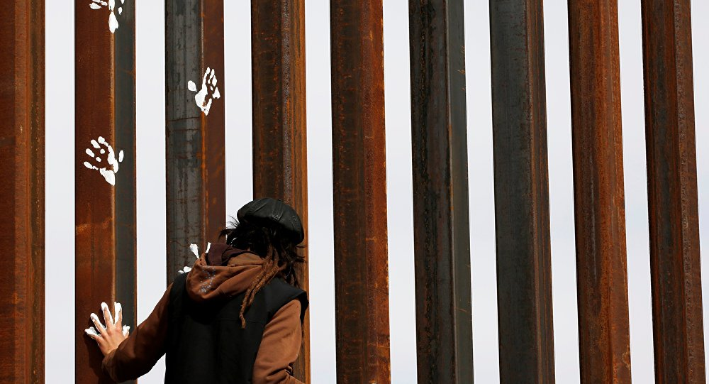 An activist paints the U.S.-Mexico border wall between Ciudad Juarez and New Mexico as a symbol of protest against U.S. President Donald Trump's new immigration reform in Ciudad Juarez, Mexico February 26, 2017.