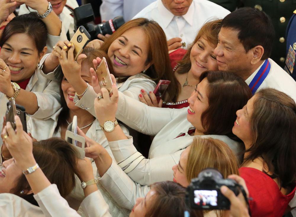 Des femmes font une selfie avec le président philippin Rodrigo Duterte à la cérémonie de prestation de serment du chef de la Garde nationale philippine