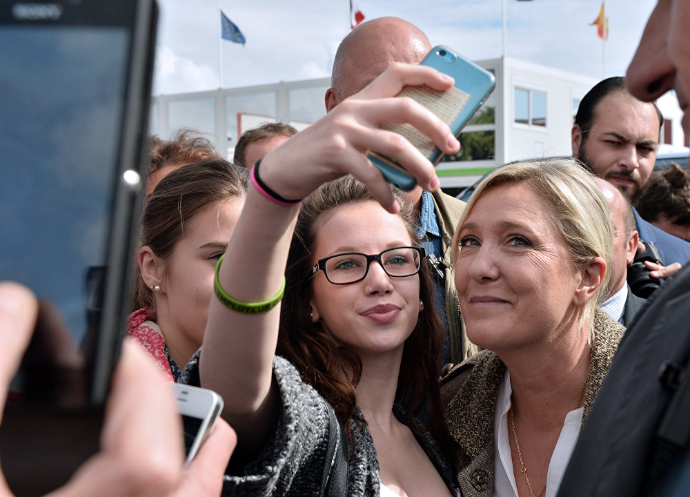 La leader du Front national Marine Le Pen pose pour une photo avec une visiteuse à l'Exposition internationale d'élevage en France