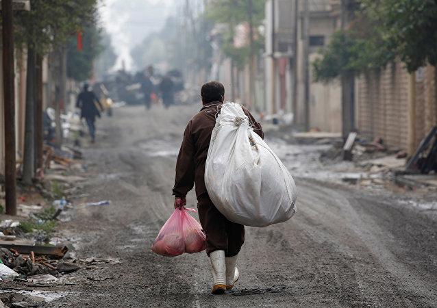 Un homme irakien porte des marchandises de l'aide humanitaire dans le district d'Al Ghizlane alors que la lutte contre les terroristes de l'État islamique se poursuit à Mosul, en Irak