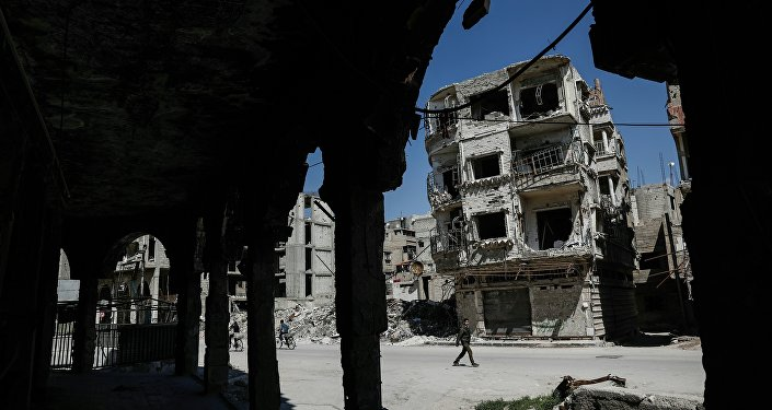 Syrians walk past damaged buildings on April 7, 2017, in the rebel-held town of Douma, on the eastern outskirts of Damascus.