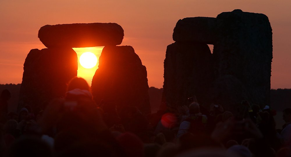 The rising sun is seen through the standing stones at the prehistoric monument Stonehenge, near Amesbury in Southern England, on June 21, 2014, as revelers gather to celebrate the 2014 summer solstice, marking the longest day of the year.