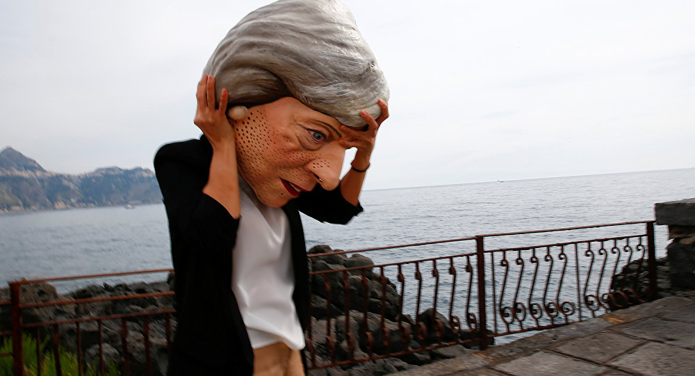 A protester wears a mask depicting Britain's Prime Minister Theresa May during a demonstration organised by Oxfam in Giardini Naxos, Sicily, Italy, May 25, 2017.