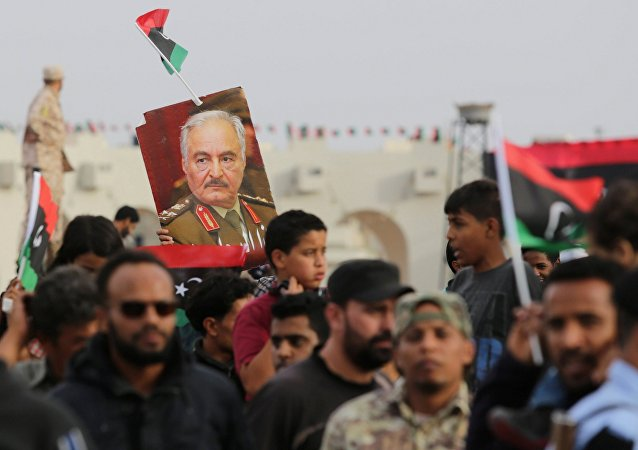 A poster of Libyan military commander Khalifa Haftar is held during celebrations marking the third anniversary of Libyan National Army's ÒDignityÓ operation against Islamists and other opponents, in Benghazi, Libya May 16, 2017.