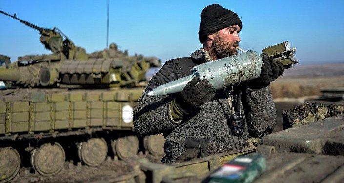 Un militaire ukrainien charge des munitions dans un char dans le Donbass
