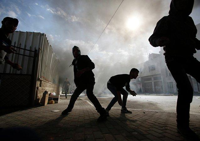 Les manifestants palestiniens se préparent à jeter des pierres aux soldats de l'armée israélienne