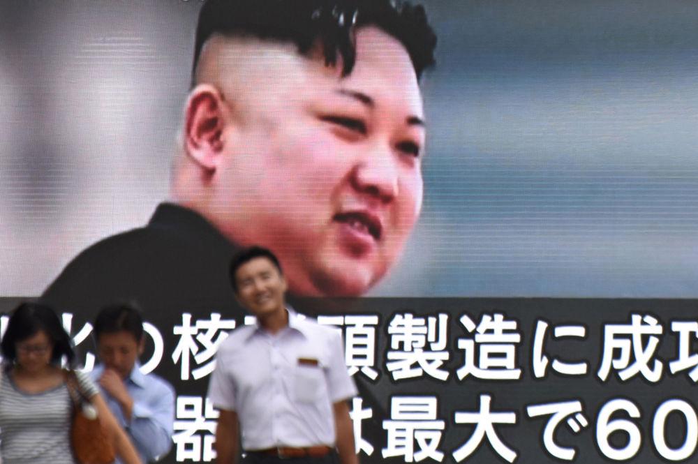 Des gens passant devant un écran géant montrant le dirigeant nord-coréen Kim Jong-un à Tokyo, au Japon