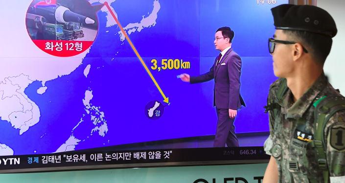 Un soldat sud-coréen passe devant un écran de télé avec une infographie montrant la distance entre la Corée du Nord et Guam, dans une gare à Séoul, le 9 août 2017