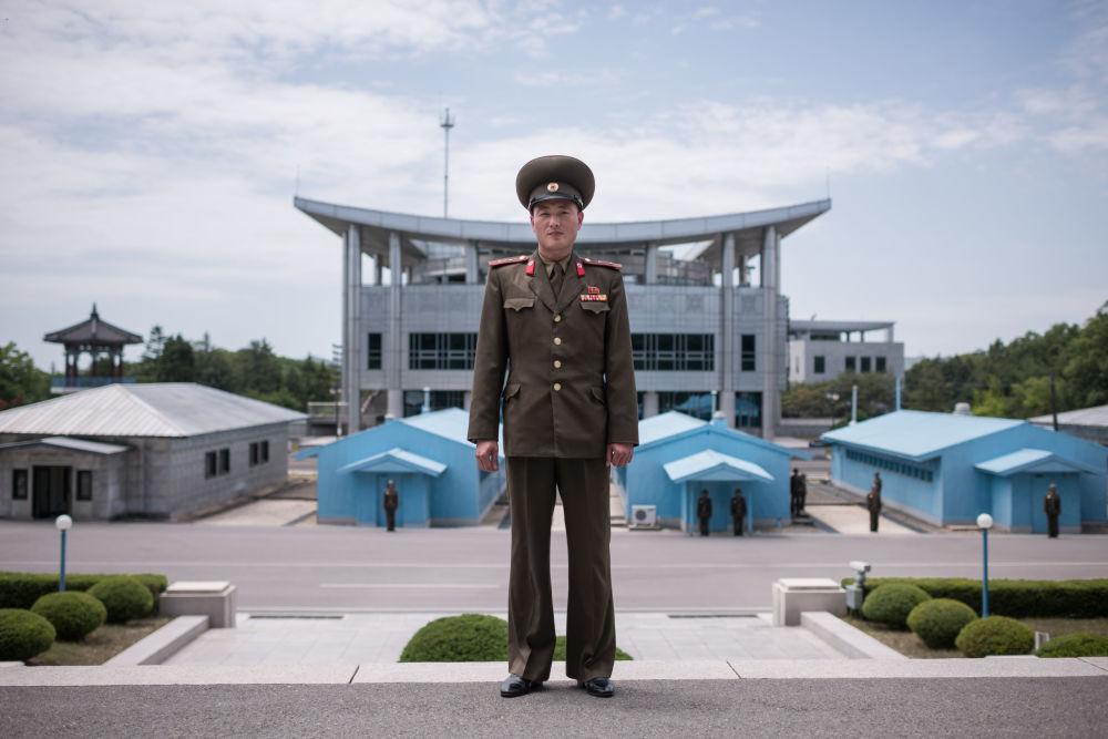 Un militaire de l'Armée populaire de Corée devant la ligne de démarcation dans la zone démilitarisée entre la Corée du Nord et la Corée du Sud