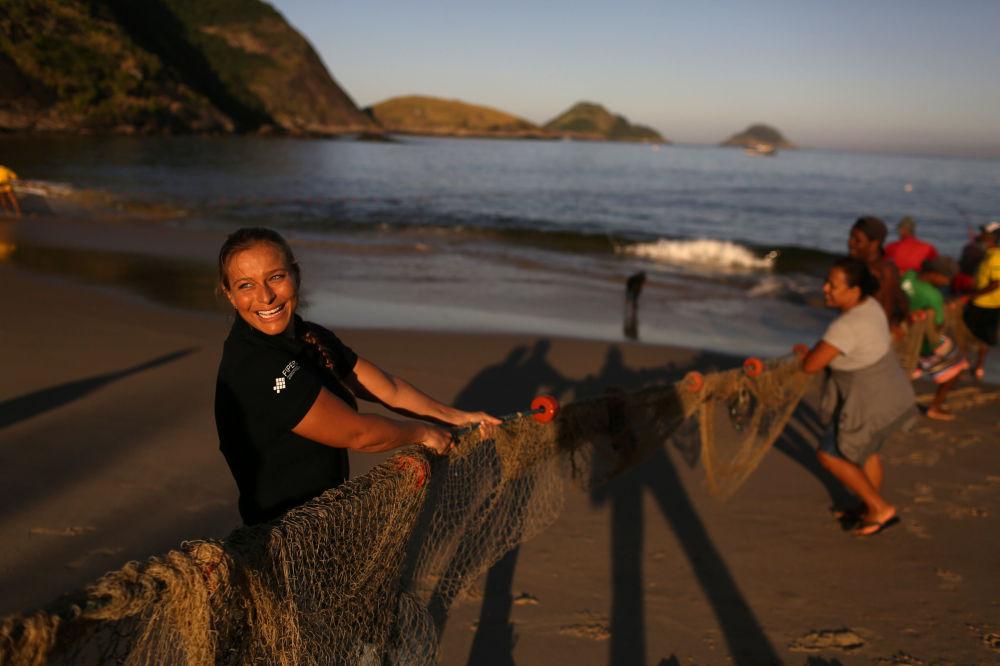 Une monitrice pour sirènes avec des pêcheurs sur une plage de Niterói, au Brésil