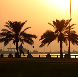 Man plays football at a corniche during sunset in Dammam, Saudi Arabia