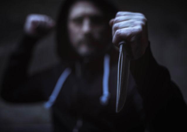 un homme armé d'un couteau (image d'illustration)