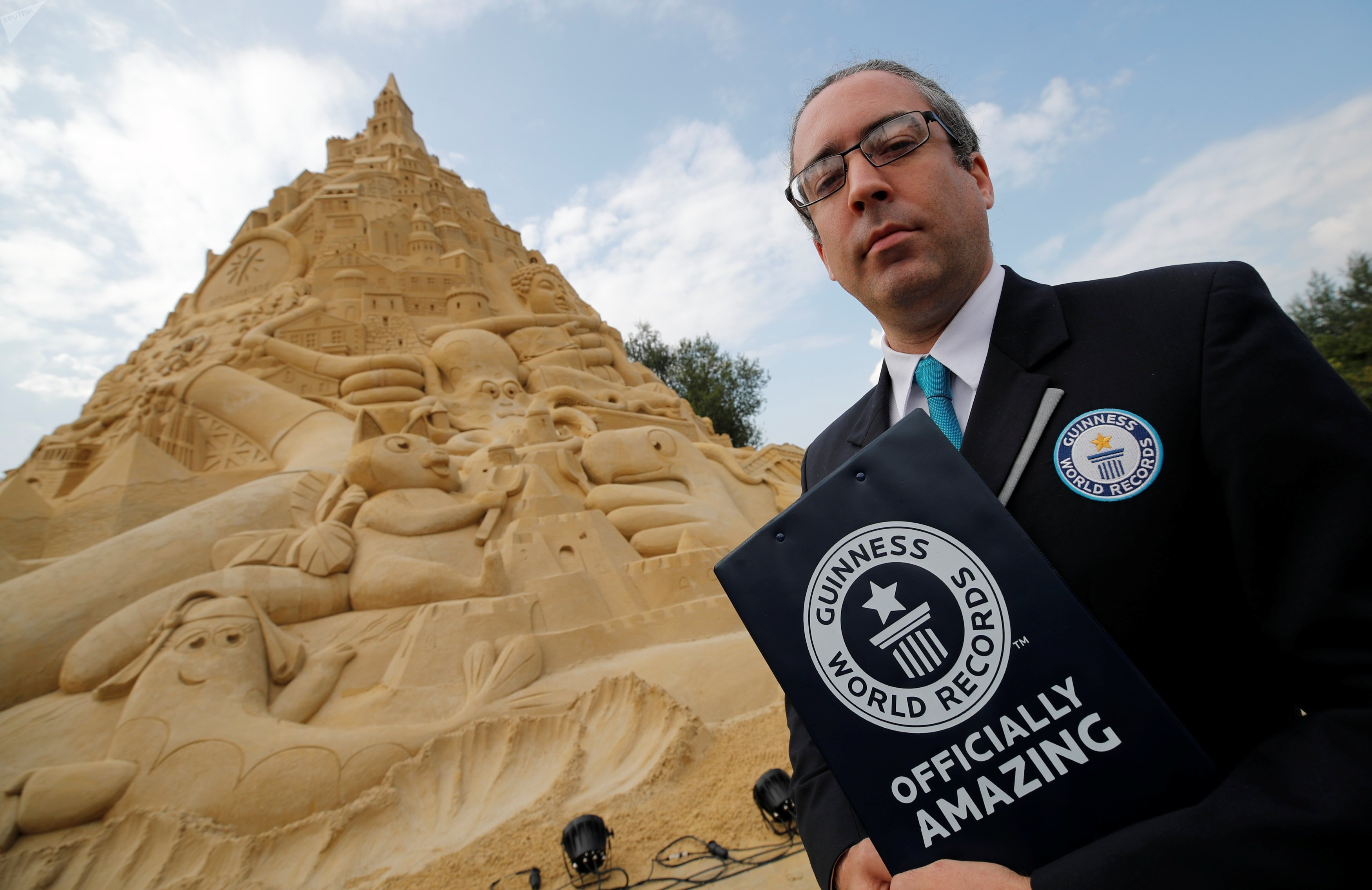 Jack Brockbank, the official judge of Guinness World Records stands next to the world's highest sandcastle (16.68 metres) in Duisburg, western Germany, September 1, 2017.