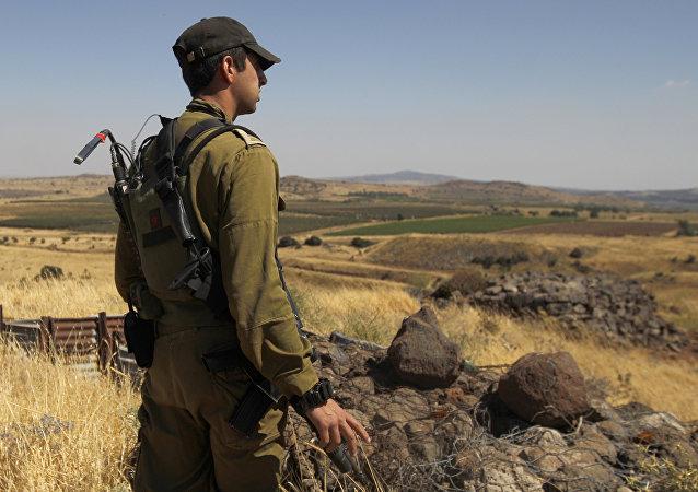 Un soldat israélien patrouille près de la frontière avec la Syrie