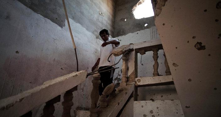 Un Libyen dans une maison endommagée par un bombardement à Syrte