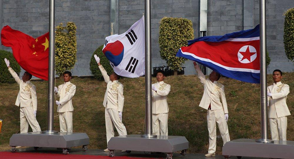 Les drapeaux sud-coréen, chinois et nord-coréen