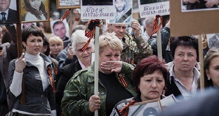 Anna Tuv, avec les portraits de son mari et sa fille, participe à une manifestation à Donetsk