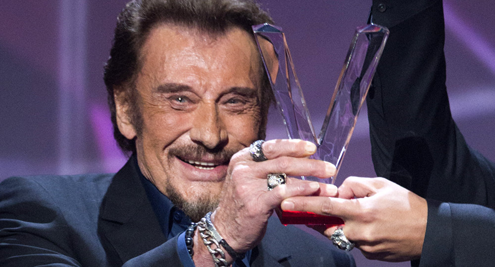 French singer Johnny Hallyday holds his trophy as he receives the best album award during the 31st Victoires de la Musique