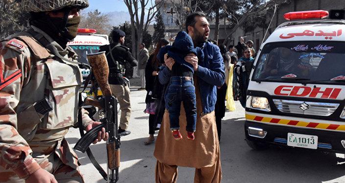 Un homme avec un enfant près d'une église chrétienne de la ville pakistanaise de Quetta attaquée par des terroristes
