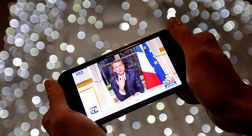 French President Emmanuel Macron is seen on the screen of an iPhone in Marseille as he gives the traditional New Year speech