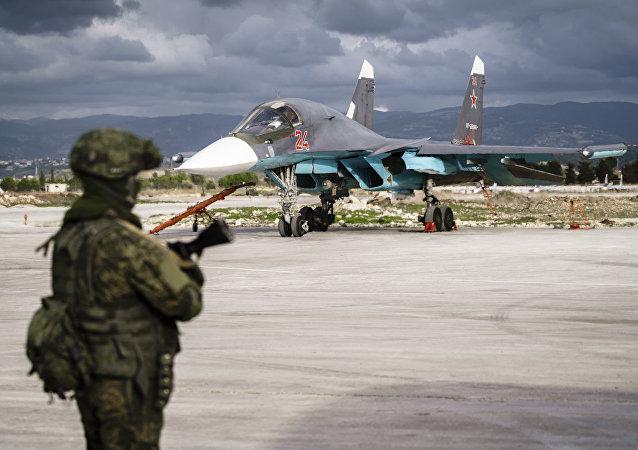 Un militaire russe devant un chasseur Soukhoï Su-34 sur la base aérienne de Hmeimim