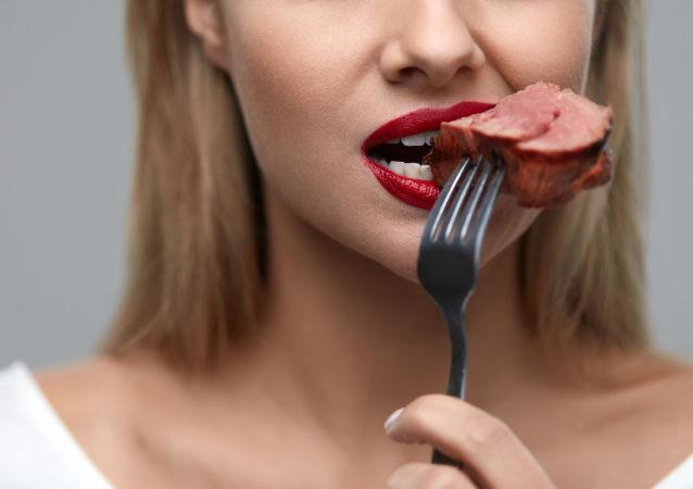 Une femme mange de la viande