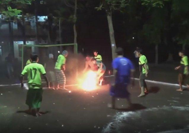 Certains l'aiment chaud: les écoliers indonésiens jouent au football avec du feu